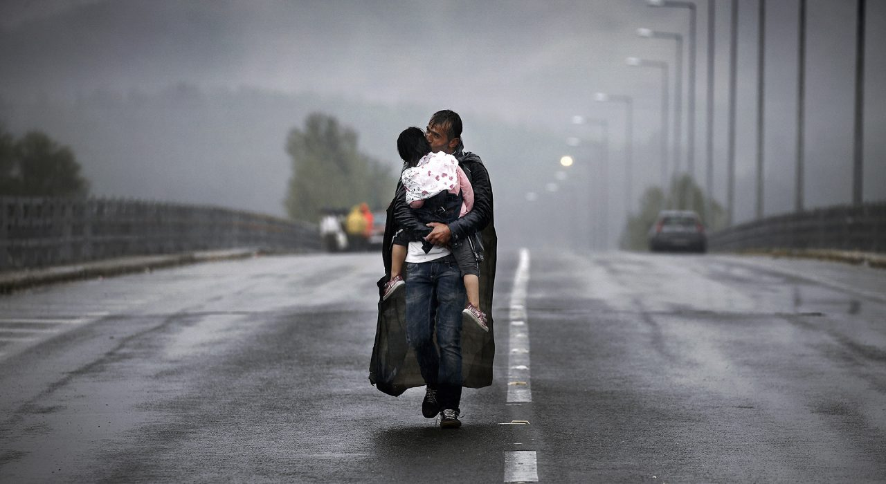 Ειδομένη, Ελλάδα 2015 ©Yannis Behrakis/Reuters Ένας Σύρος πρόσφυγας φυλάει την κόρη του καθώς περπατάει μέσα στην καταιγίδα προς τα σύνορα της Ελλάδας με τη Βόρεια Μακεδονία, κοντά στο χωριό Ειδομένη, 10 Σεπτεμβρίου 2015.